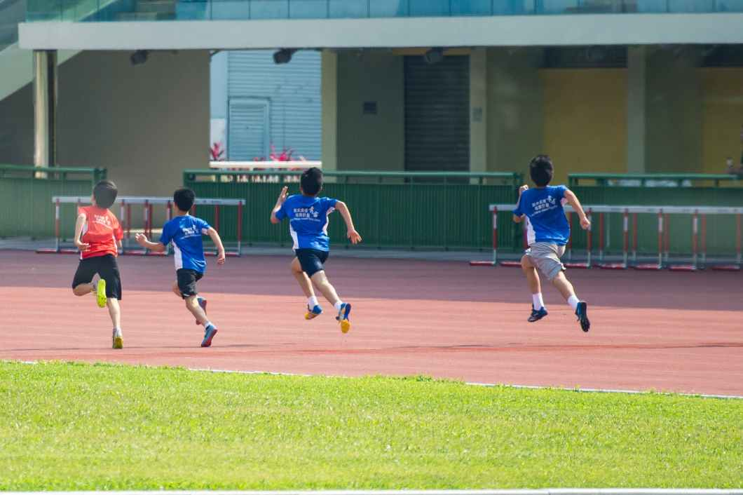 four boys running in track